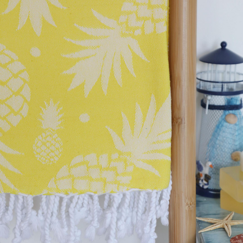 Yellow, pineapple Turkish towel has tassels at the borders