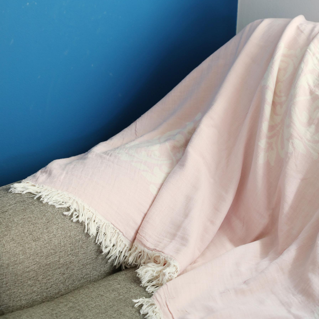 Powder-pink, cotton Turkish throw/blanket has baroque designs on it