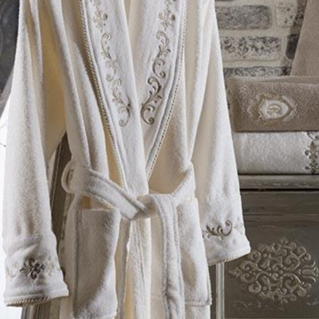 Ecru color, fluffy women`s bathrobe, ornamented  with golden bronze color embroideries on collars and cuffs