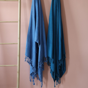 Two Turkish beach towels in marine-blue and petrol-blue colored hanging on a wall