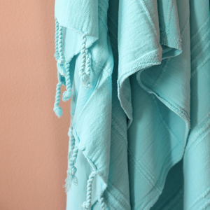 Soft, turquoise color Turkish beach/bath towel has hand-tied tassels