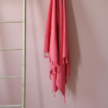 Load image into Gallery viewer, Stone-washed, vermilion red Turkish peshtemal hanging on a wall