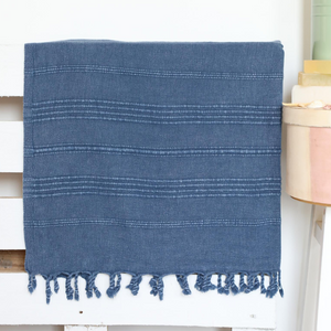 Stone-washed, navy Turkish beach/bath towel on a bed frame