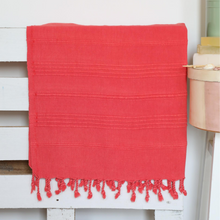 Load image into Gallery viewer, Vermilion-red color Turkish beach/bath towel on a bed frame