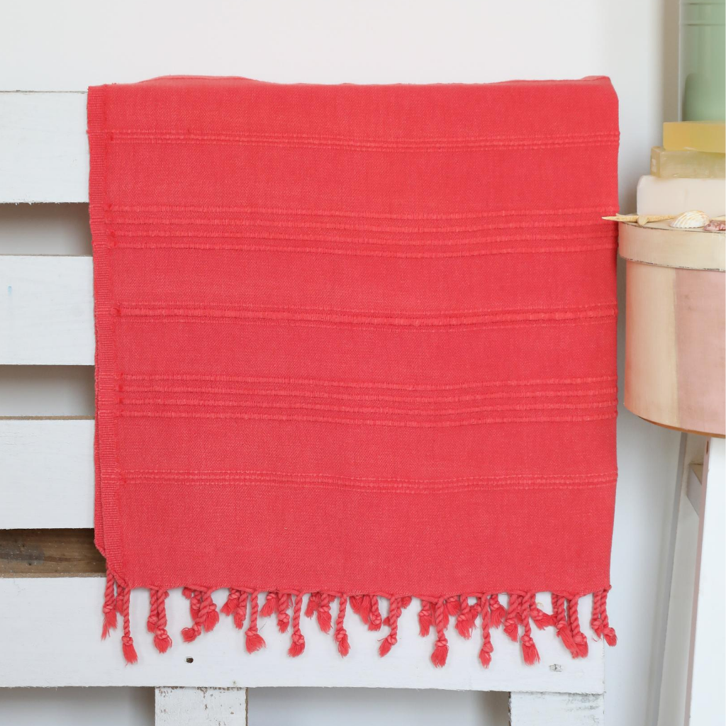 Vermilion-red color Turkish beach/bath towel on a bed frame