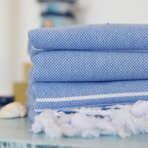 Blue, light-weight Turkish bath towels on a table