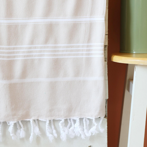 beige color peshtemal towel with white stripes and tassels