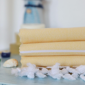 Yellow Turkish towels has white stripes and tassels