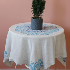Linen table cloth is hand-crafted with blue, floral designs made by wood-block printing