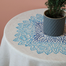 Load image into Gallery viewer, Floral designs in tones of blue on a linen table cloth