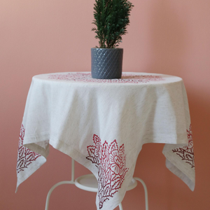 Linen table cloth has red, floral designs made by traditional hand printing