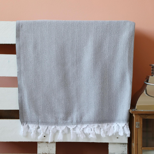 Grey, cotton Turkish towel on a bed frame