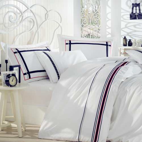 Minimalist bedroom decorated with white bed linen set which has navy and red lines at borders