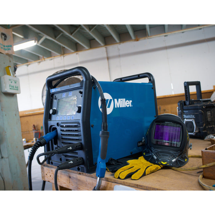 The Millermatic 255 on a work bench with helmet and gloves