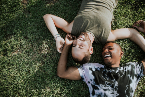 Men lay together on the grass with arms entwined. There's not always a big difference between a fling and a relationship.
