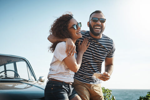 A man and a woman show the definition of a fling with their big smiles and casual energy.