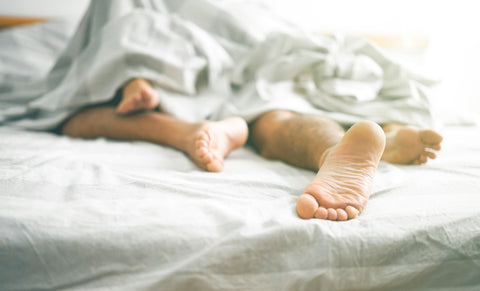 Two people in bed, experiencing maximum pleasure thanks to our oral sex tips.