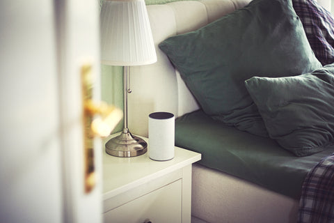 A speaker on a bedside table ready to play music to enhance the oral sex experience