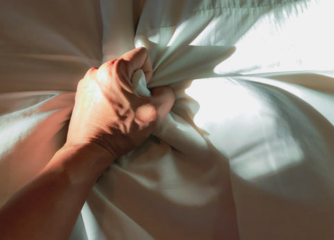A person grabbing the bed sheets, in the midst of an orgasm.