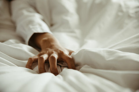 A person in bed, in the midst of complete oral sex ecstasy.