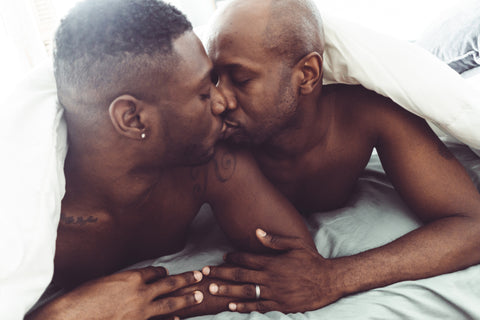 A male couple in bed, preparing to try our oral sex tips for ultimate pleasure.