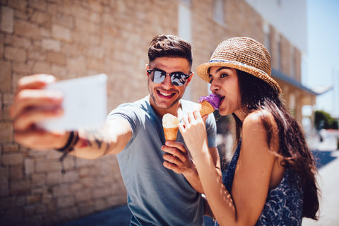 A young couple takes a selfie while eating ice cream on a sunny day showing that yes, flings are good!