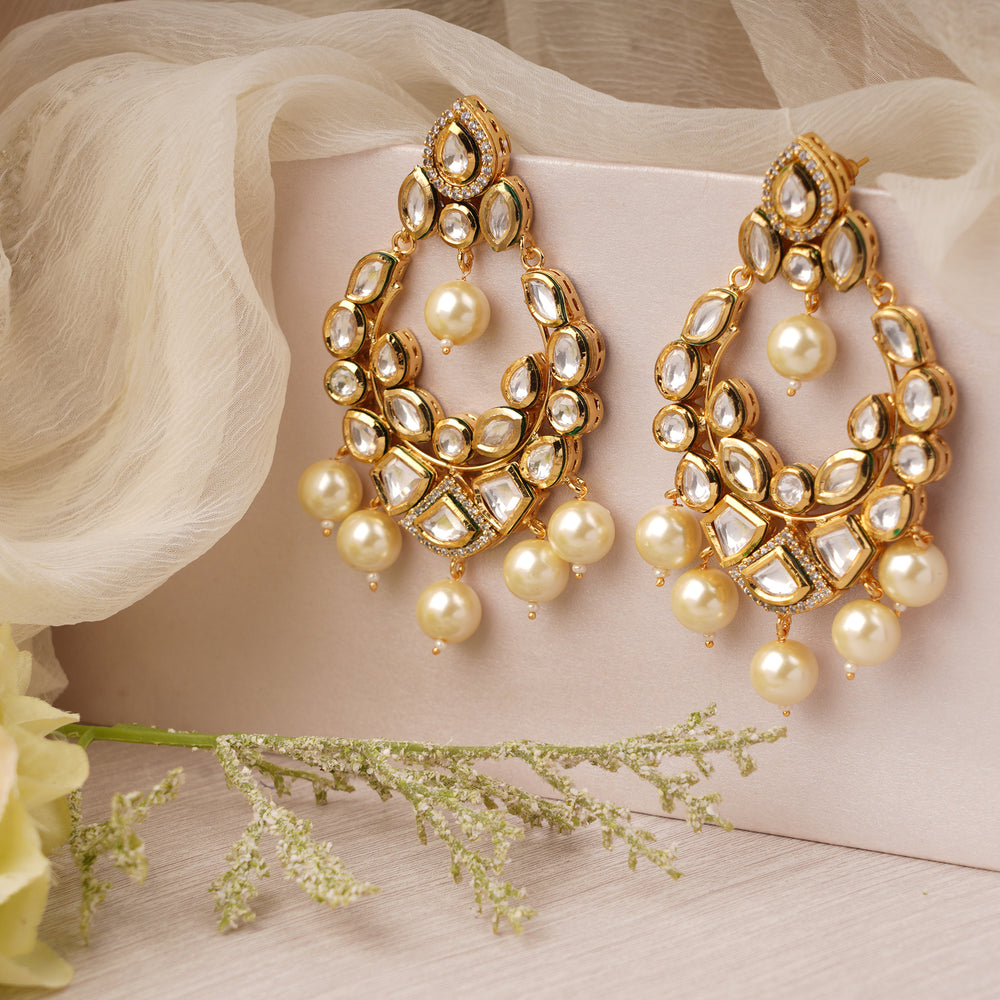 Gold plated kundan earrings with faux pearls and meenakari work at the back.