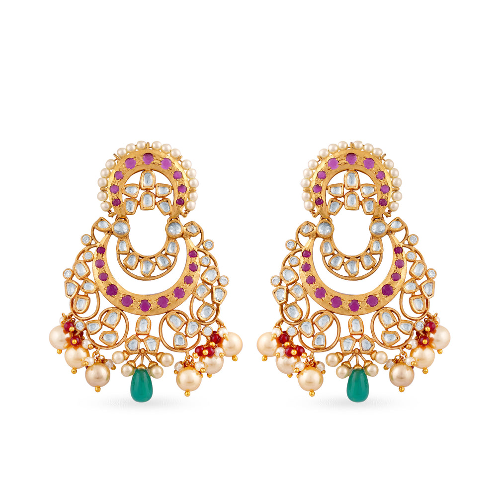 Gold plated kundan chaandbaali earrings with little ruby stones outline and a green stone drop.