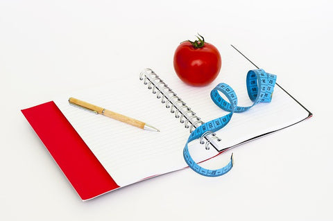 notebook with pen, tape measure and tomato