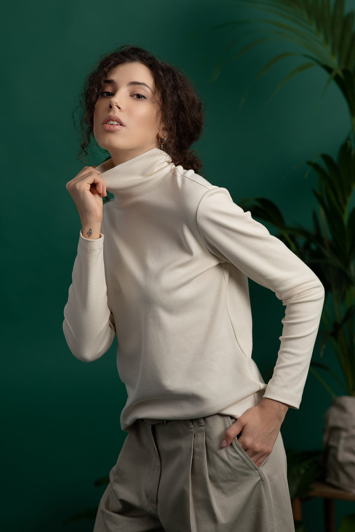 A model in beige ecological turtleneck - Dolce Vita and beige eco trousers. Ethical and sustainable ECO fair fashion