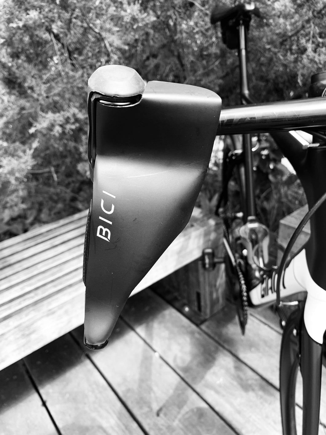 Close up of road bike handlebars with the newest must have winter cycling accessory, The Bici Shield, attached to its brake lever. This streamlined black abs hand protector shields a riders hands from the cold while cycling in the winter.