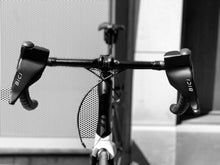 Load image into Gallery viewer, A closeup of a roadbike's handlebars with two Bici Shields attatched. These sleek, black plastic wind guards are designed to protect cyclist's hands while riding their bike in the cold.