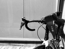 Load image into Gallery viewer, A side profile of a white road bike with Bici cold weather hand protectors attached to its brake levers. These black plastic hand protectors shield a cyclists hands from wind, rain, and cold, allowing them to ride their bike in the winter months.