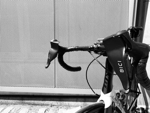 The handlebars of a white roadbike with black handlebars with two bici shields attached to its brake levers, photographed in front of a metal mesh wall.