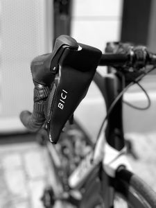 Bici Shield installed on the brake lever of a roadbike's handlebars showing white bici logo and black hand protector