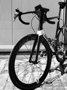 Black roadbike with two Bici Shields attached to the brake levers of its handlebars to protect hands from cold weather and wind