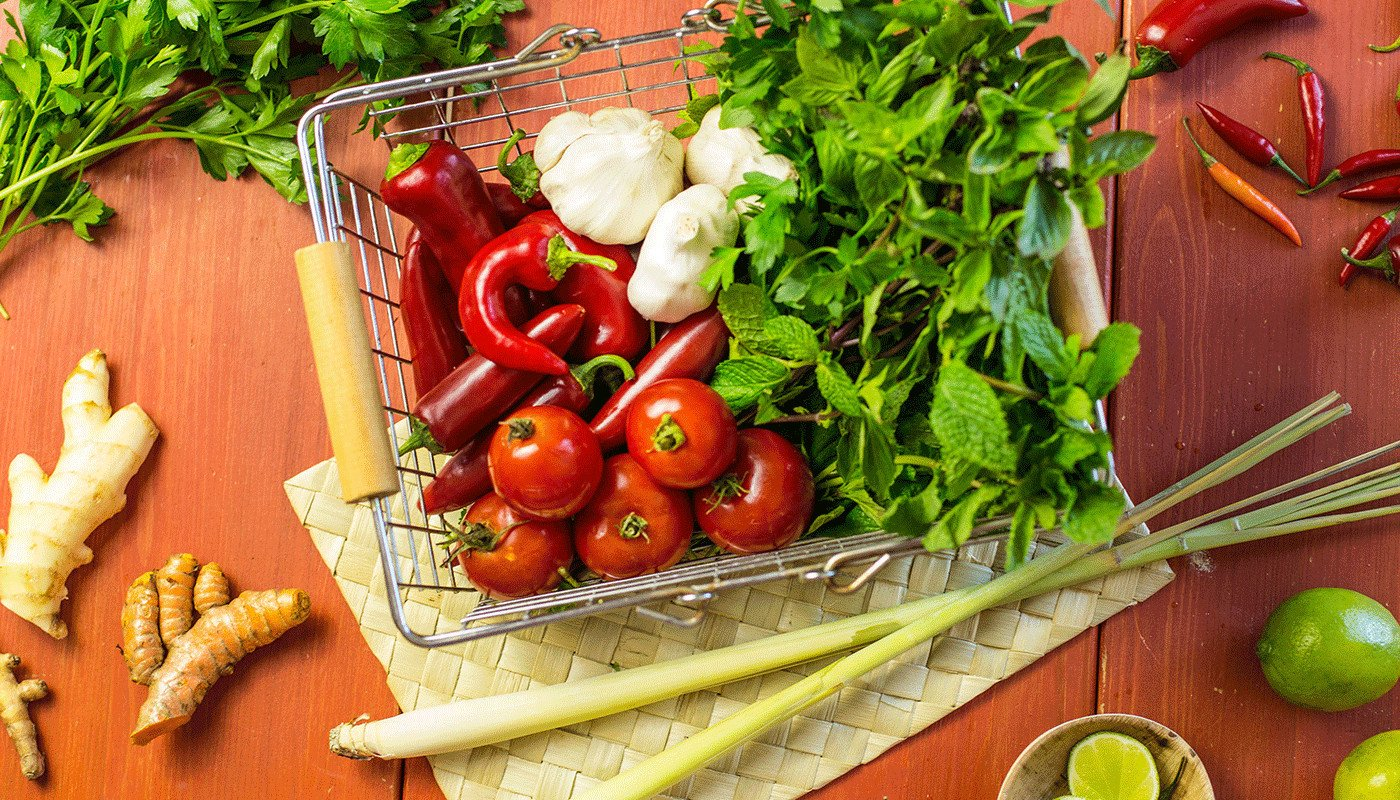 Basket of peppers, garlic, and greens sitting on top of a woven placemat with ginger root, limes, and other greens off to the side.