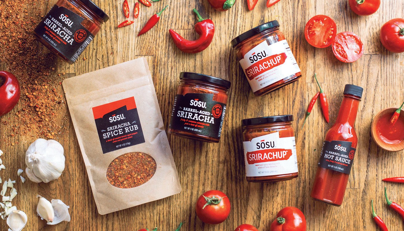 Various Sosu Sauces products including spice rubs, barrel-aged sriracha in jars, hot sauce, and ketchup spread out on a tabletop with garlic cloves, tomatoes, peppers, and spices throughout.