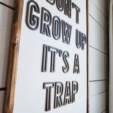 Don't grow up it's a trap wood sign