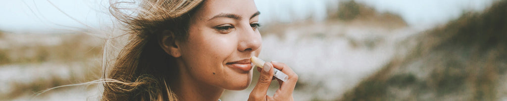 Woman applying natural lip balm