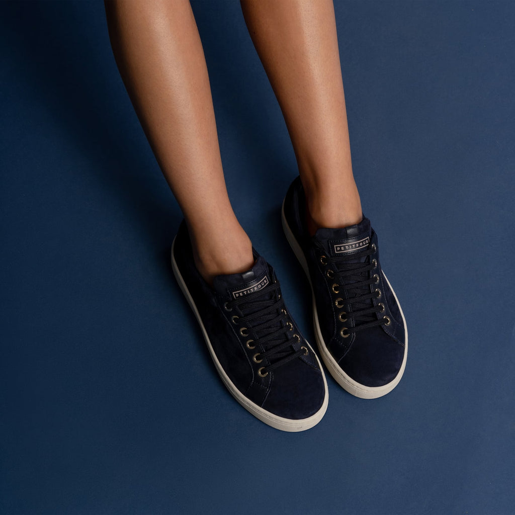 female legs with feet shod in blue sneakers blueberry petite size shoes model from petitfour feeling good collection