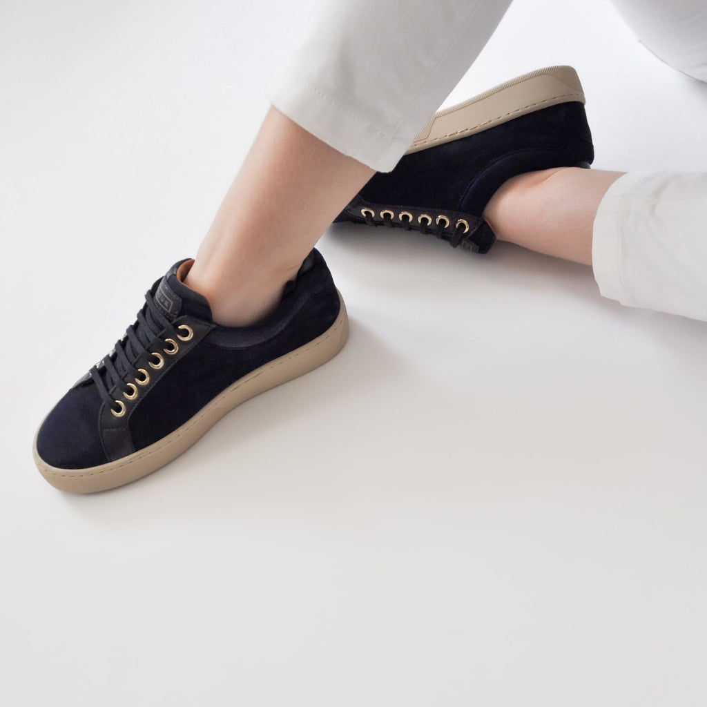 female seated down with feet shod in blue sneakers blueberry small size shoes model from petitfour feeling good collection