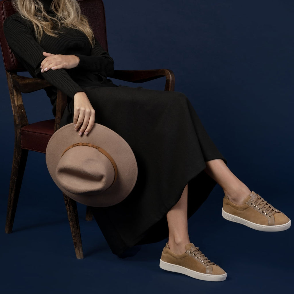 female side seated down with feet shod in beige sneakers caramel small size shoes model from petitfour feeling good collection