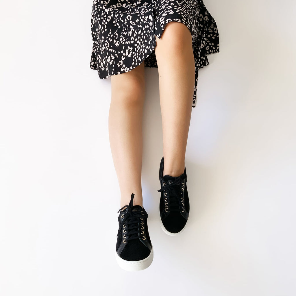 female laid down with feet shod in black sneakers liquorice small size shoes model from petitfour feeling good collection