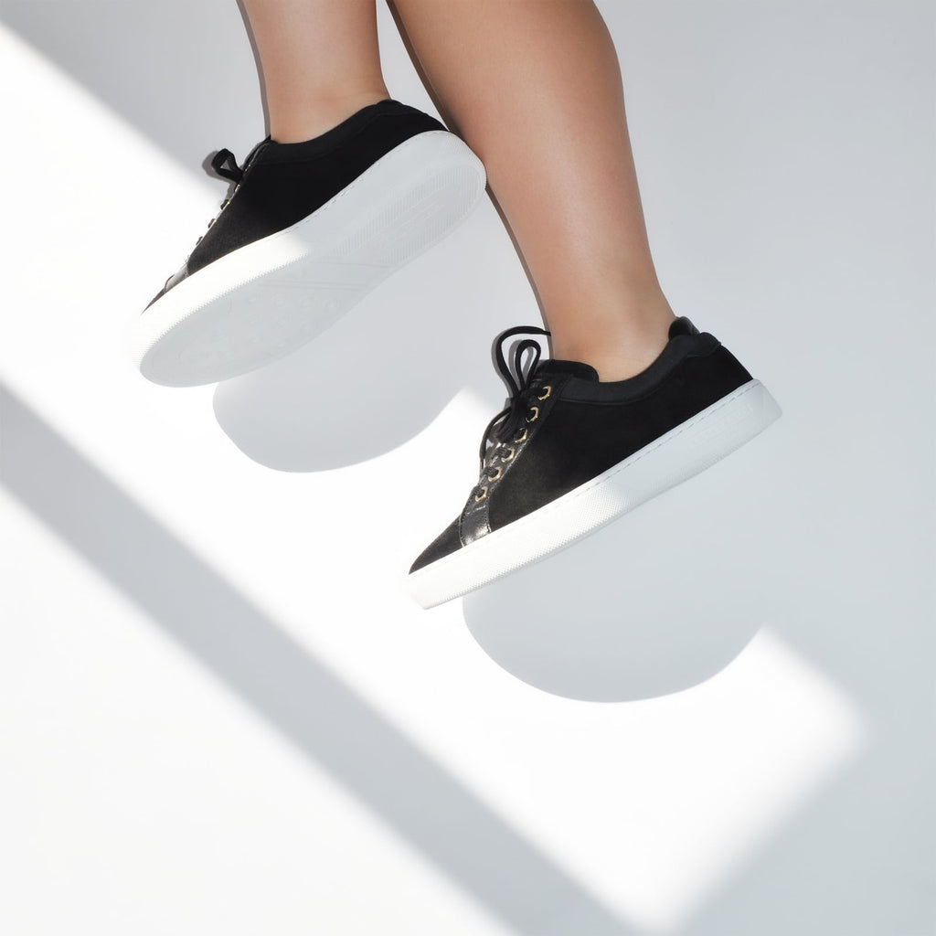 female side legs with feet shod in black sneakers liquorice petite size shoes model from petitfour feeling good collection