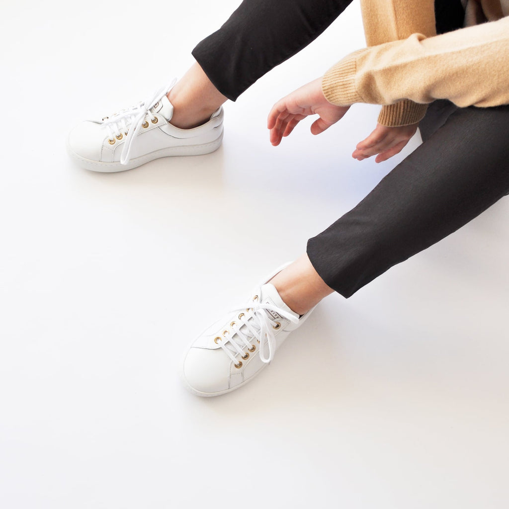 female seated down with feet shod in white sneakers marshmallow small size shoes model from petitfour feeling good collection