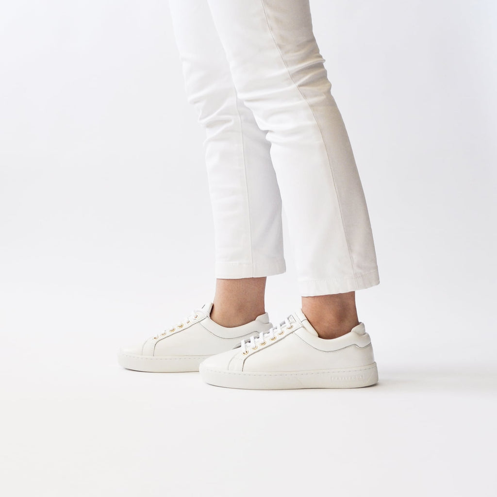 female legs with feet shod in white sneakers marshmallow petite size shoes model from petitfour feeling good collection