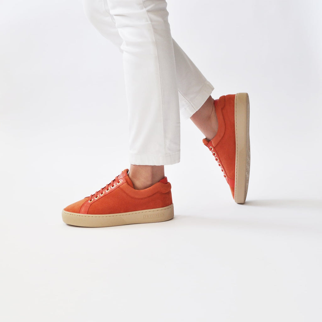 female walking with feet shod in orange sneakers papaya small size shoes model from petitfour feeling good collection