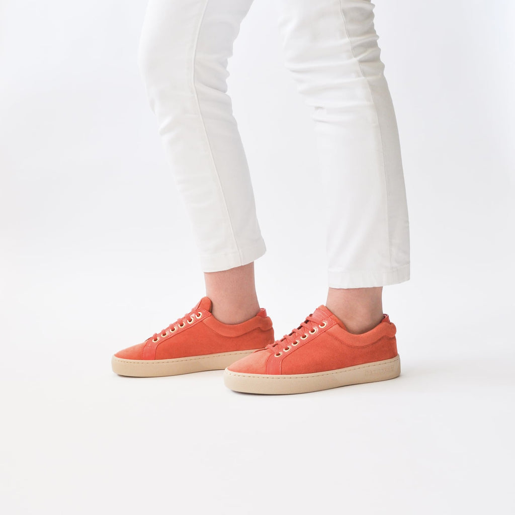 female legs with feet shod in orange sneakers papaya petite size shoes model from petitfour feeling good collection