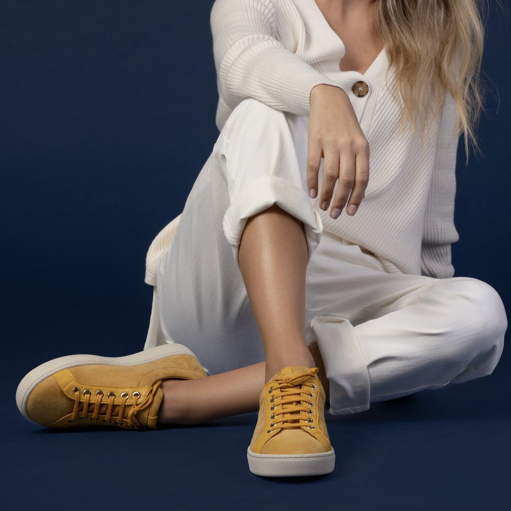 female seated down with feet shod in yellow sneakers saffron small size shoes model from petitfour feeling good collection
